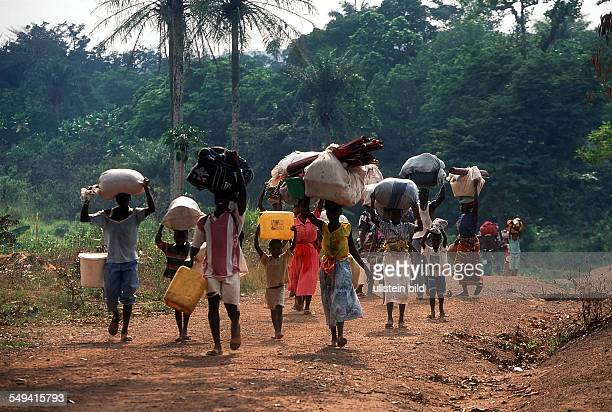 GIN Guinea refugees from Sierra Leone on their way from the refugee camp Mongo to Conakry They bear her possessions on their head