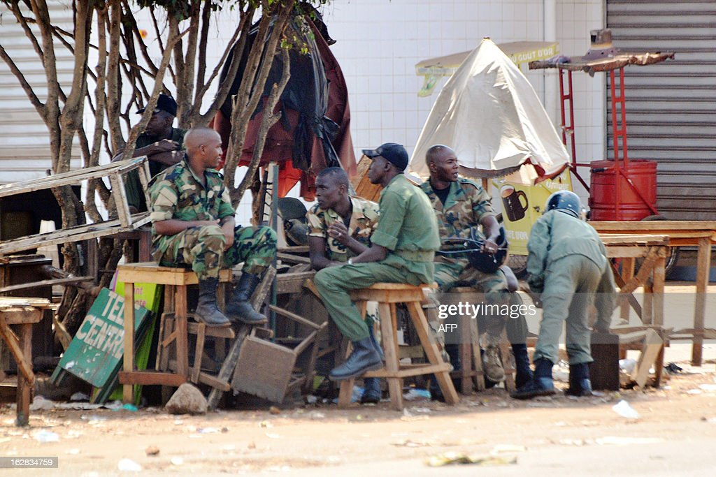 Guinean gendarmes sit on February 28, 2013 at the Cosa intersection in Conakry, where some of the violence broke out on February 27 during a Guinean opposition demonstration. Some 130 people were wounded, including 68 police, on February 28 in the latest in a string of opposition demonstrations to demand transparency in elections scheduled for May 12 and protest against the South African company selected to revise the electoral roll.