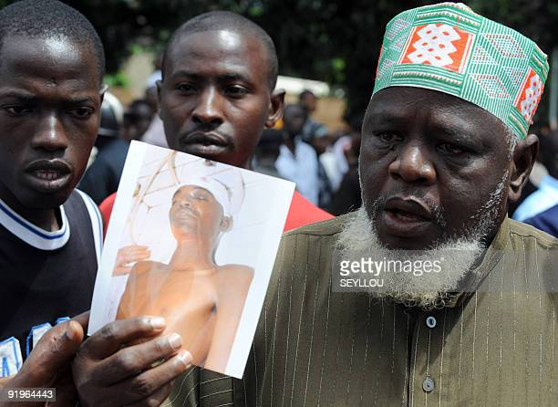 A Guinean man shows a picture of his son killed during the 28 September demonstration as he stands on October 2 2009 in front of the Conakry great...