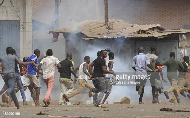 Guinean opposition supporters run during clash with anti riot policemen on April 13 2015 in Conakry Several protesters were wounded on April 13 as...