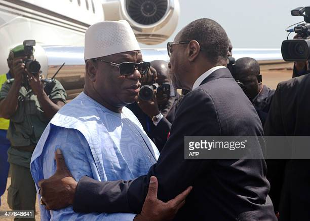 Guinean president Alpha Conde hugs his Malian counterpart Ibrahim Boubacar Keita upon his arrival on March 10 2014 at Conakry airport Ibrahim...