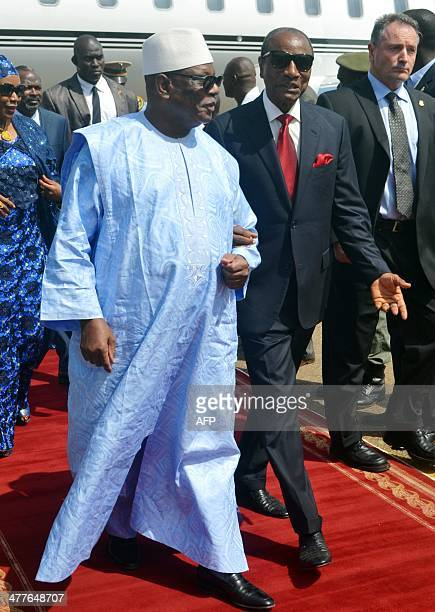 Guinean president Alpha Conde welcomes his Malian counterpart Ibrahim Boubacar Keita upon his arrival on March 10 2014 at Conakry airport Ibrahim...