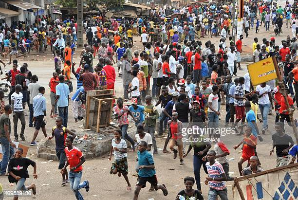 Guinean protesters run during clash with antiriot police on April 13 2015 in Conakry Several protesters were wounded on April 13 as Guinean police...
