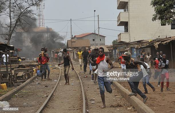 Guinean protesters run during clash with antiriot policemen on April 13 2015 in Conakry Several protesters were wounded on April 13 as Guinean police...