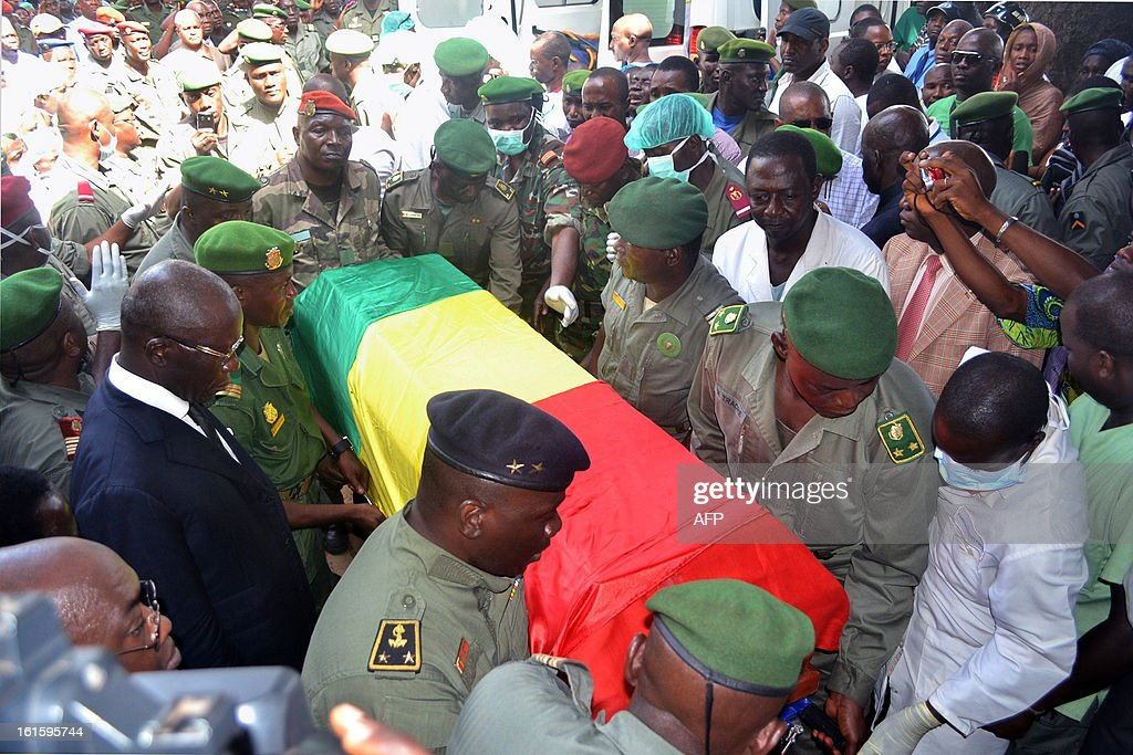 Guinean soldiers carry the coffin of army chief of staff, General Souleymane Kelefa Diallo, on February 12, 2013 at an air base outside Conakry, where the victims of the February 11, 2013 plane crash in the Liberian town of Charlesville were repatriated. A plane carrying a military delegation from Guinea crashed on February 11 in Charlesville, killing the army chief of staff, General Souleymane Kelefa Diallo, and 10 other people. The plane was carrying the delegation to attend an armed forces day in Liberia, which holds ceremonies each year to recognize its military and often invites officers from neighbouring countries, including Guinea.