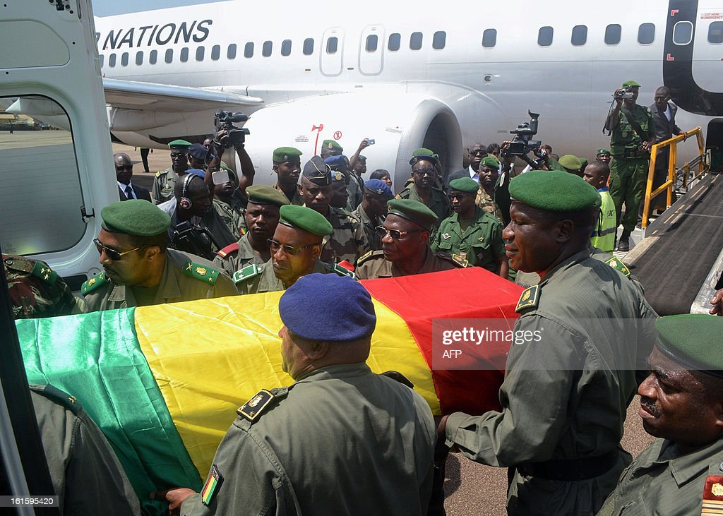 Guinean soldiers carry the coffin of the army chief of staff, General Souleymane Kelefa Diallo, on February 12, 2013 at an air base outside Conakry, where the victims of the February 11, 2013 plane crash in the Liberian town of Charlesville were repatriated. A plane carrying a military delegation from Guinea crashed on February 11 in Charlesville, killing the army chief of staff, General Souleymane Kelefa Diallo, and 10 other people. The plane was carrying the delegation to attend an armed forces day in Liberia, which holds ceremonies each year to recognize its military and often invites officers from neighbouring countries, including Guinea. AFP PHOTO / MAMADOU CELLOU DIALLO