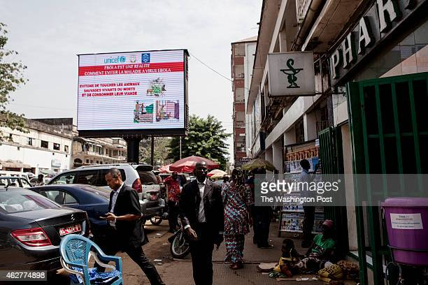 Guineans walk passed an electronic signboard promoting Ebola awareness in Conakry Guinea on Tuesday January 27 2015