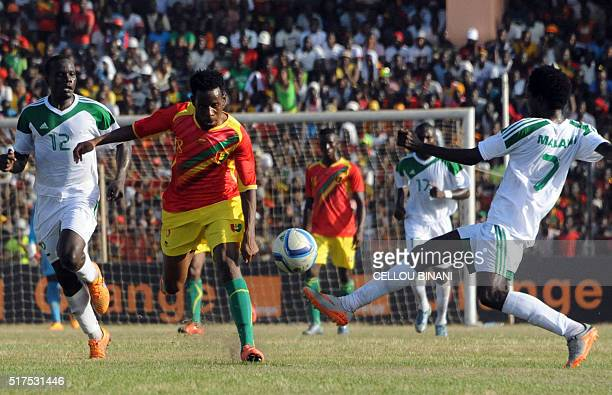 Guinea's Ibrahim Traore vies with Malawi's players Chimando Kayira and Hawvy Nyvanda during the 2017 African Cup of Nations qualification football...