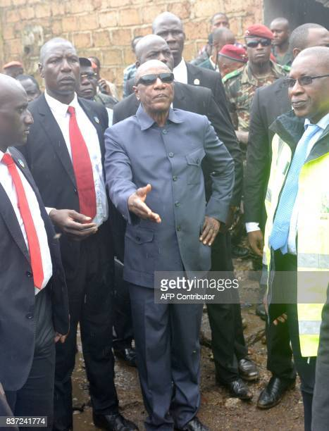 Guinea's President Alpha Conde arrives on the site where eight people died and dozens were injured in the West African state of Guinea when a rubbish...