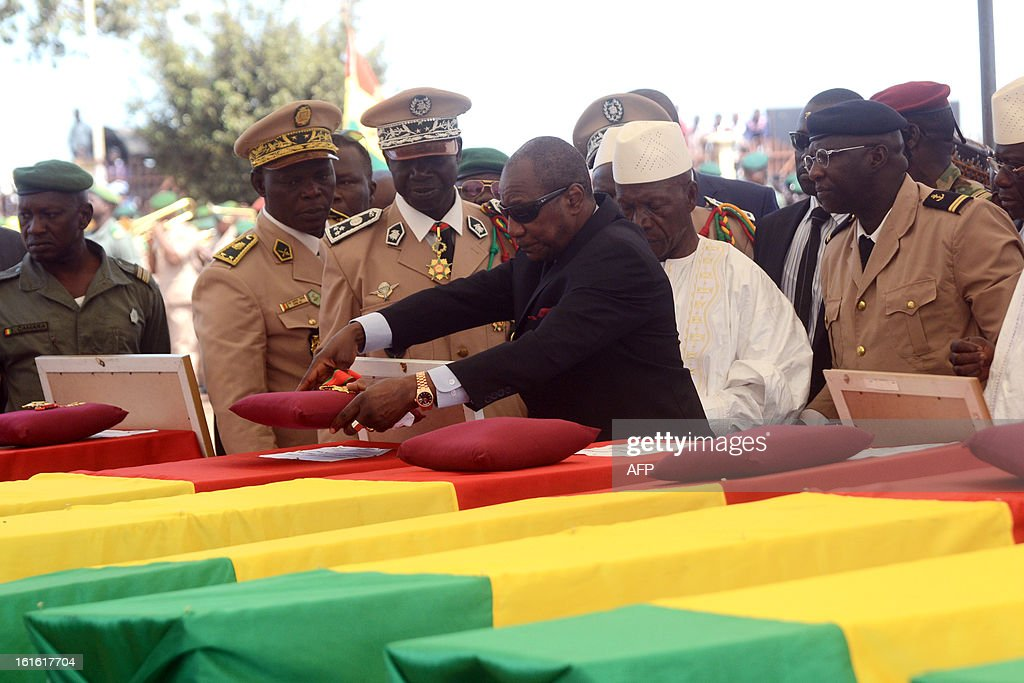 Guinea's President Alpha Conde (C), surrounded by General and Chief of Cabinet at the Defence Ministry, Aboubacar Sidiki Camara (C,L) and Guinea's Prime Minister Mohamed Said Fofana (C,R), decorates the coffins of the victims of a plane carrying a military delegation from Guinea that crashed two days ago in the Liberian town of Charlesville, killing the army chief of staff and 10 other people, during a ceremony in Conakry on February 13, 2013. AFP PHOTO / CELLOU BINANI