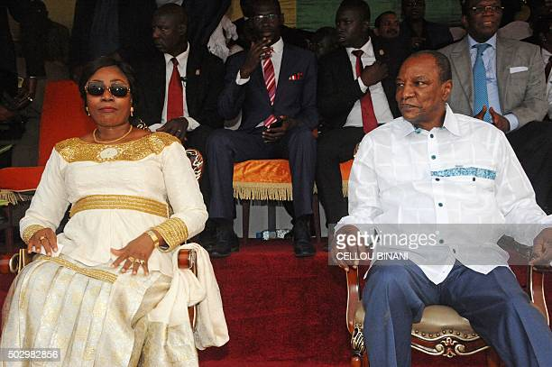 Guinea's president Alpha Konde and Guinea's First Lady Djene Kaba Conde look on during the 'Bye bye Au revoir Ebola' concert on December 30 2015 in...