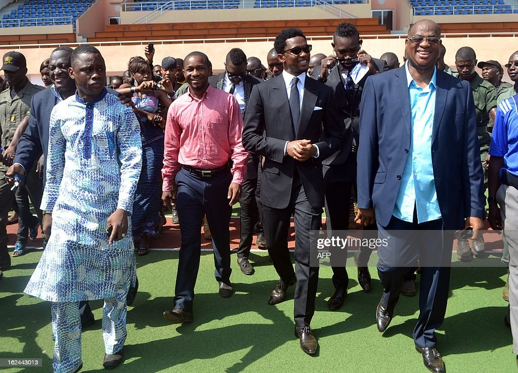 Guinea's Sport Minister Sanoussi Banthma Sow (L), Cameroon's football star Samuel Eto'o (C) and Guinea's football federation president Salifou Camara (R) walks the 'Srade de l'Unite' stadium on Febuary 23, 2013 in Conakry. Samuel Eto'o is on two day visit to Guinea.