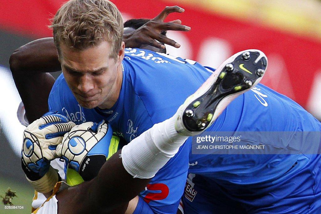 Guingamp's Danish goalkeeper Jonas Lossl (R) catches the ball despite of Monaco's Ivoirian forward Lacina Traore (hidden) during the French L1 football match Monaco (ASM) vs Guingamp (EAG) on April 30, 2016, at the Louis II stadium in Monaco.