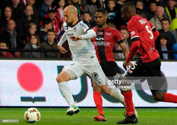 Guingamp's French defender Marcus Coco vies with Guingamp's Senegalese midfielder Moustapha Diallo and Metz' French midfielder Renaud Cohade during...