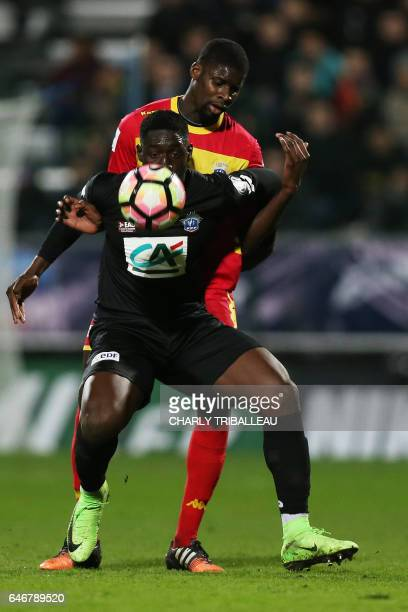 Guingamp's French defender Marcus Coco vies with Quevilly Rouen's French Senegalese midfielder Oumar Pouye during the French Cup football match...