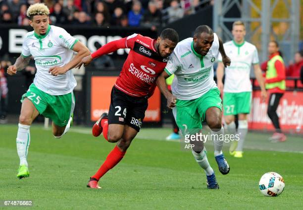 Guingamp's French defender Marcus Coco vies with SaintEtienne's French defender Kevin Malcuit and SaintEtienne's French defender Kevin...
