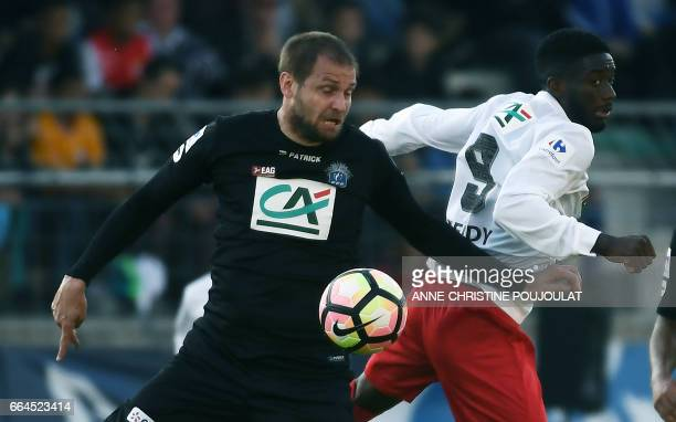 Guingamp's French defender Mathieu Bodmer vies with FrejusSaint Raphael's Neupoc Mendy during the French Cup final quarter football match between...
