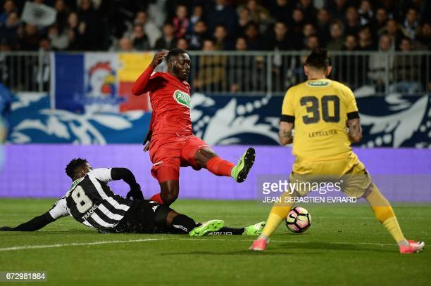 Guingamp's French forward Alexandre Mendy vies with Angers' Ivorian defender Ismael Traore and Angers' French goalkeeper Alexandre Letellier during...