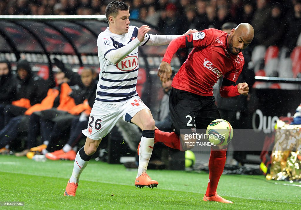 Guingamp's French forward Jimmy Briand (R) vies with Bordeaux's French defender Frederic Guilbert during the French L1 football match Guingamp against Bordeaux on February 13, 2016 at the Roudourou stadium in Guingamp, western France. / AFP / FRED TANNEAU