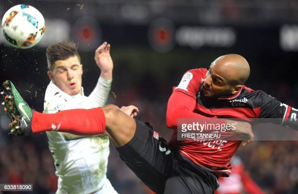 Guingamp's French forward Jimmy Briand vies with Caen's French defender Frederic Guilbert during the French L1 football match Guingamp against Caen...