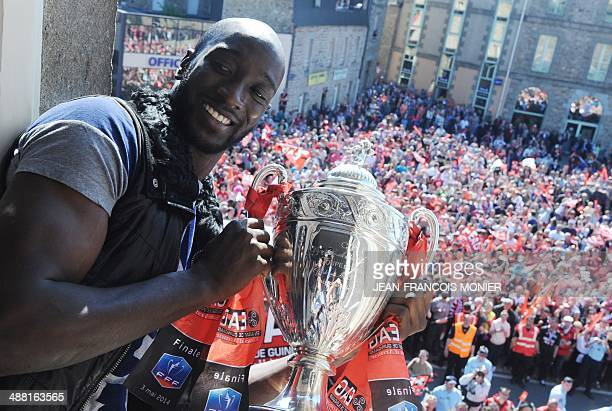 Guingamp's French forward Mustapha Yatabare holds the Coupe de France trophy as he celebrate along with Guingamp's players and fans from a City Hall...