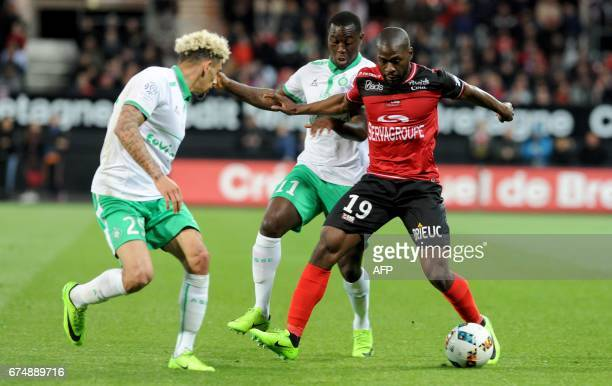 Guingamp's French forward Yannis Salibur vies with SaintEtienne's French defender Kevin Malcuit and SaintEtienne's French midfielder Yohan Mollo...