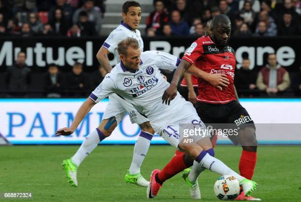 Guingamp's French forward Yannis Salibur vies with Toulouse's Sewdish forward Ola Toivonen during the French L1 football match between Guingamp and...