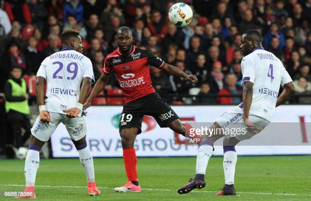 Guingamp's French forward Yannis Salibur vies with Toulouse's Swiss defender Jacques François Moubandje and Toulouse's Malien midfielder Tongo...