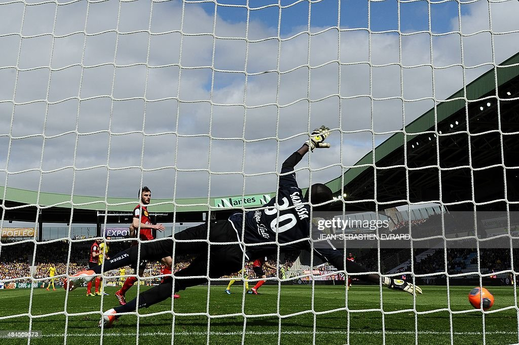 Guingamp's French goalkeeper Mamadou Samassa tries to stop the ball as Nantes' Togolese forward Serge Gakpe (unseen) scores a goal during the French L1 football match between Nantes and Guingamp on April 13, 2014 at the Beaujoire stadium in Nantes, western France.
