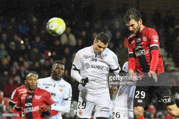 Guingamp's French midfielder Christophe Kerbrat heads the ball and scores a goal despite Dijon's French forward Benjamin Jeannot during the French L1...