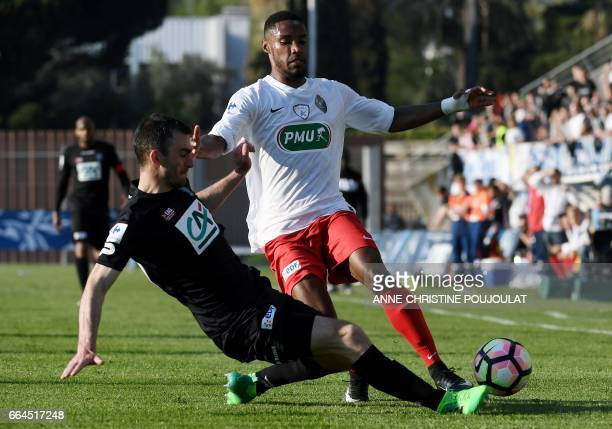 Guingamp's French midfielder Christophe Kerbrat vies with FrejusSaint Raphael's defender Fernando Marcal De Oliveira during the French Cup final...