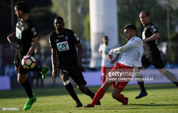 Guingamp's French midfielder Christophe Kerbrat vies with FrejusSaint Raphael's forward Karim Tlili reacts during the French Cup final quarter...