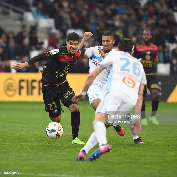 Guingamp's French midfielder Ludovic Blas vies for the ball with Olympique de Marseille's French midfielder William Vainqueur and Olympique de...