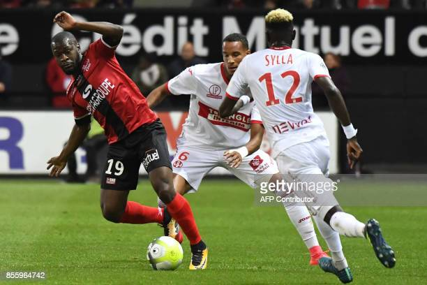 Guingamp's French midfielder Yannis Salibur vies with Toulouse's French defender Christopher Jullien and Toulouse's Guinean defender Issiaga Sylla...