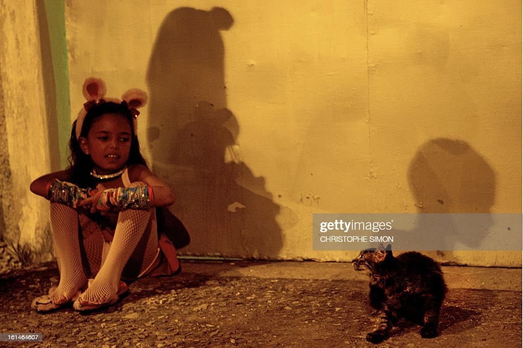 A guirl fancy dressed as a 'gatinha' (pussycat) stares at a real pussycat as she awaits take part in the local 'Indio' carnival group of the Guadalupe neighborhood in northern Rio de Janeiro, Brazil, in their 'Bate Bola' traditional parade on February 10, 2013. AFP PHOTO/Christophe Simon