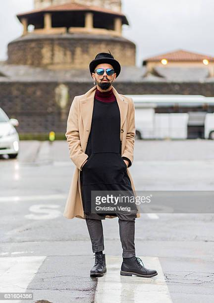 Guiseppe Pisani is wearing a beige wool coat black hat sunglasses oversized long shirt ankle leather boots on January 13 2017 in Florence Italy