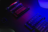 Close-up electric guitar body part with gradient lighting effect.