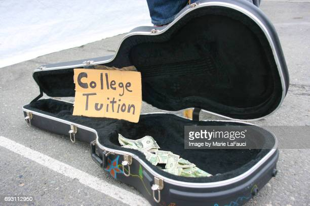 Guitar case open with money for tips with 'College Tuition' sign