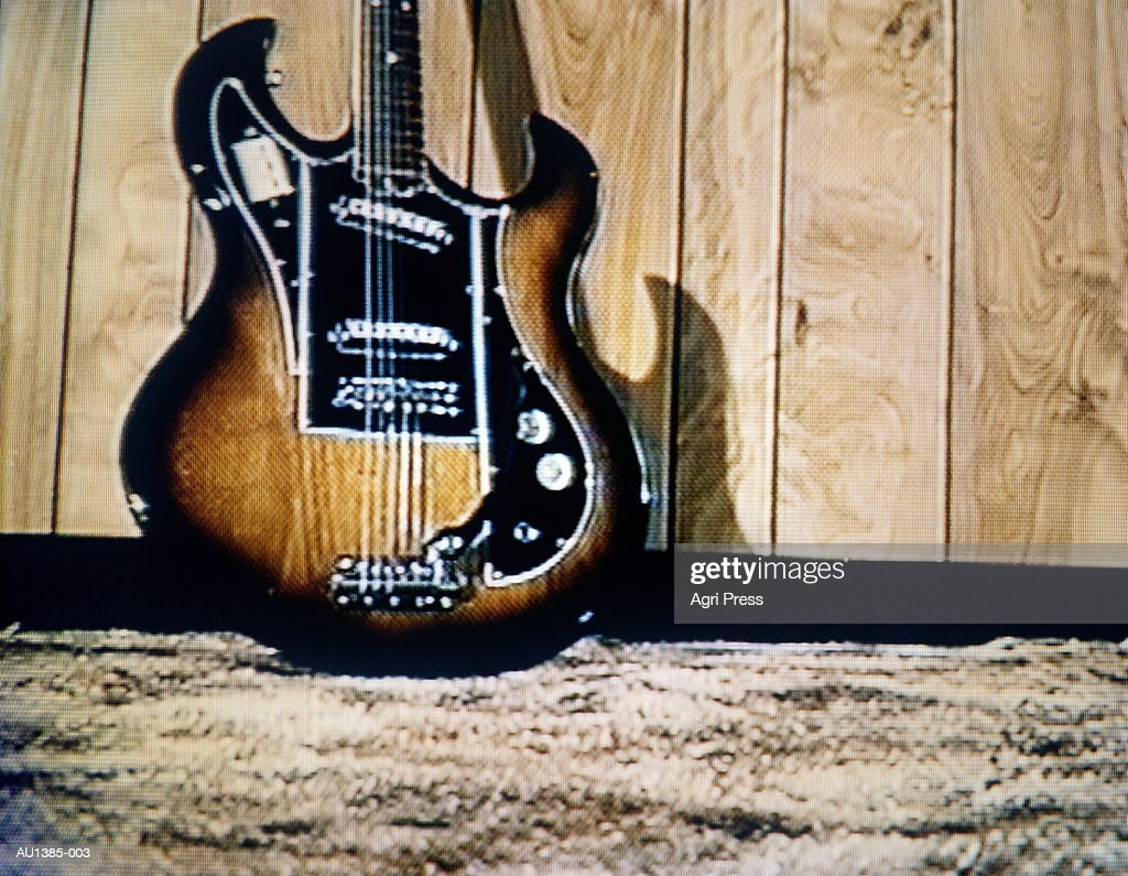 Guitar leaning on wood panel wall (video still) : Stock Photo