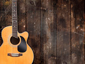 A shiny acoustic guitar resting against a rustic wooden background with moody lighting. All branding and labels have been removed.