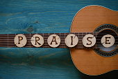 guitar on teal wooden background with wood pieces on it lettering the word: PRAISE