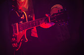 Electric guitar player on a stage with red scenic illumination, soft selective focus