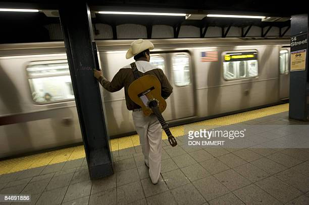 A guitar player waits to board the train at the subway station at Union Square January 30 2009 in New York Scores perhaps hundreds of freelance...