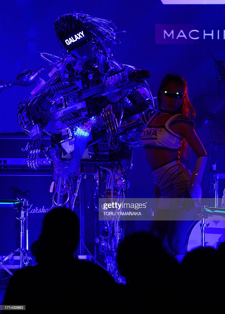 Guitar robot 'Mach' (L) of robot rock band 'Z-MACHINES' performs with a dancer during its debut concert in Tokyo on June 24, 2013. The robot band consists guitar robot 'Mach', drum robot 'Ashura' and keyboard robot 'Cosmo'. AFP PHOTO/Toru YAMANAKA