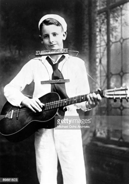 Guitarist and inventor Les Paul poses for a portrait holding a guitar and the neckworn harmonica holder he invented in circa 1929