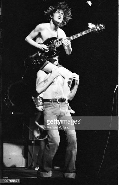 Guitarist Angus Young of Australian rock band AC/DC being carried on the shouilders of singer Bon Scott while performing on stage at the Town Hall in...