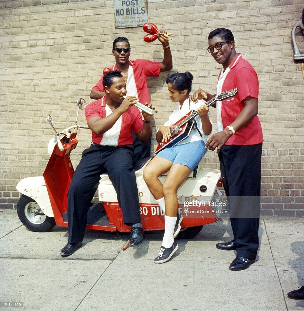 Guitarist Bo Diddley with his band, including the Duchess aka Norma Jean-Wofford on guitar and Jerome Green holding the maracas, pose for a portrait on a scooter in September 1959 in New York City, New York.