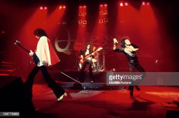 Guitarist Brian May bassist John Deacon drummer Roger Taylor and singer Freddie Mercury of British rock band Queen performing on stage in 1974