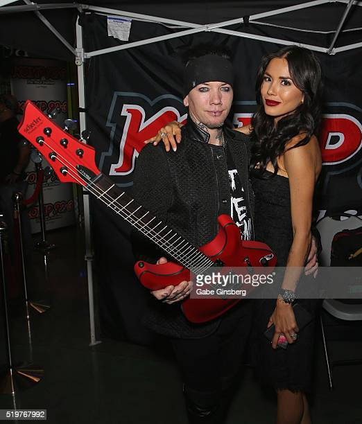 Guitarist Dj Ashba of SixxAM and his wife model Nathalia Henao pose with a guitar during the grand opening of their Ashba Clothing Store at the...