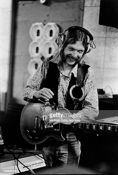 Guitarist Duane Allman of the Southern rock group the 'Allman Brothers' takes a swig of some liquor between takes as he holds his Gibson Les Paul...